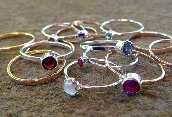Sterling silver and gold filled stacking rings with gemstone settings.