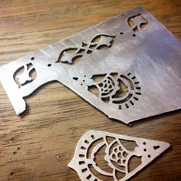 Fretwork sawn into sterling silver sheet with a fine jeweller's saw before the outlines are cut out.
