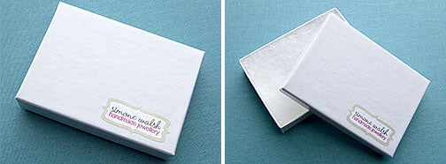 Jewellery packaging made from sturdy white recycled card and filled with cotton for padding.