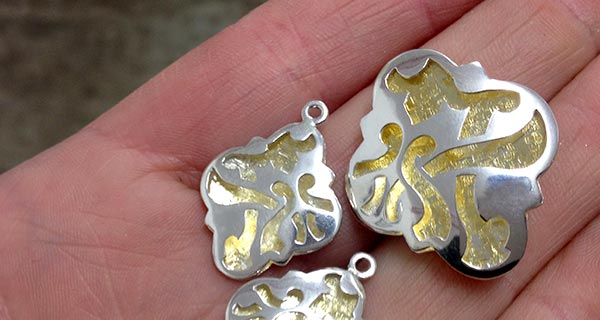 Handmade quatrefoil fretwork pendant and earring panels in sterling silver and 23ct gold gilding.