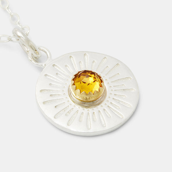 Sterling silver sunburst amulet pendant with citrine gemstone and solid gold setting.