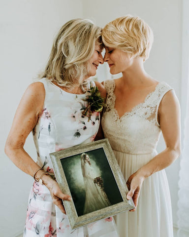 mother handing down wedding dress to daughter