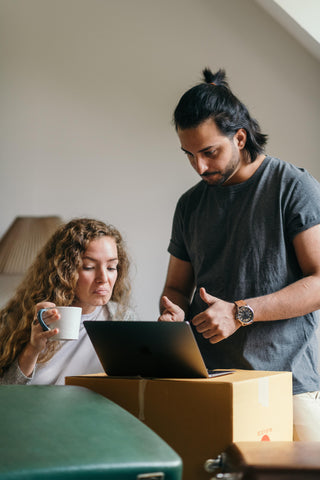 couple with moving boxes on laptop
