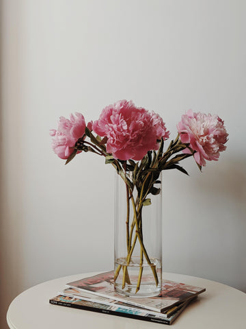vase of pink flowers on stack of magazines