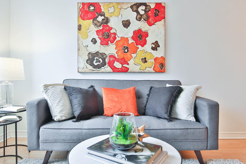 gray couch with colorful pillows and artwork