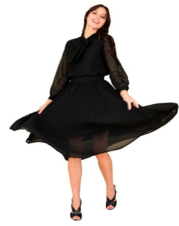 A Model Posing in a Business Casual Outfit of a Black Blouse and Pleated Skirt