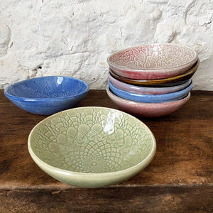A grouping of small porcelain Brewery Pottery bowls handmade from slabs of clay textured with vintage lace. When in the kitchen, we love and use these little catch all ceramics bowls for salsas, dips, hummus, ice cream, small snacks, and even those tiny leftovers.