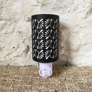 These delicately detailed ceramic night lights are a great addition to any room in the house.A thin layer of opaque black porcelain is cast on top of white translucent porcelain. Carefully the black is etched away in select areas, revealing the white porcelain underneath, creating a high contrast 3-dimensional pattern.