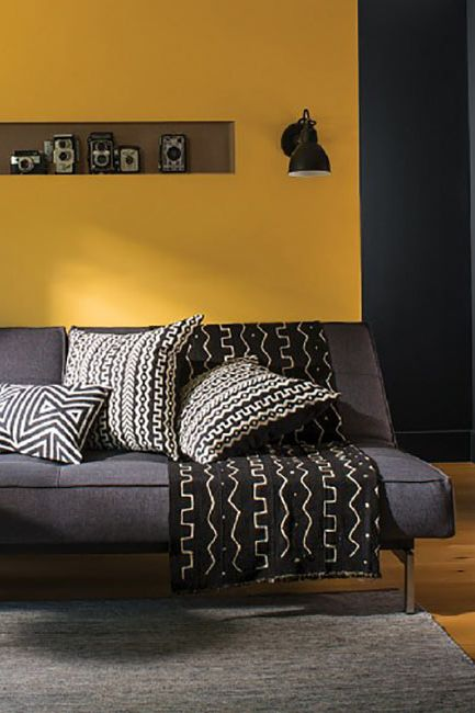 A bold yellow accent wall frames an armless sofa with geometric patterned throw pillows.