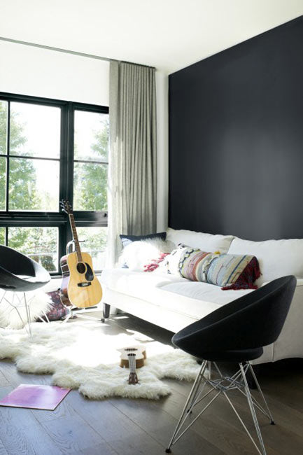 A white couch sits in front of a sleek black accent wall flanked by black chairs.