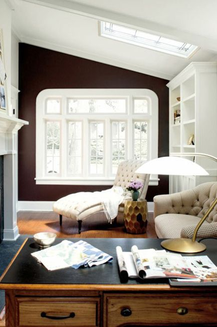 An elegant, bright office space with a large fireplace and a striking brown accent wall.