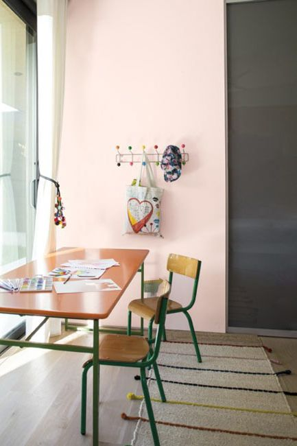 A flush pink accent wall brightens a child's desk space.