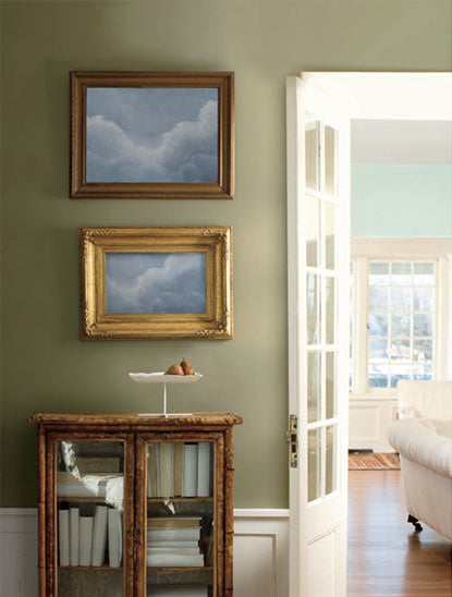 A soft, neutral green accent wall framed by a wooden console.