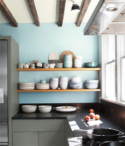 A residential kitchen with two exposed wooden shelves showcase bowls and plates against a light blue colored wall.