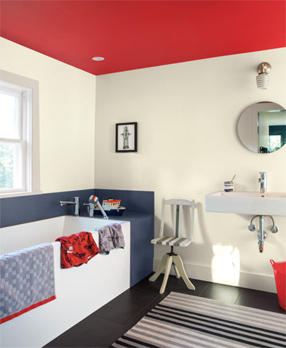 A  bathroom features a round mirror over a contemporary sink; black and white colored walls and floors are accented by a red ceiling.