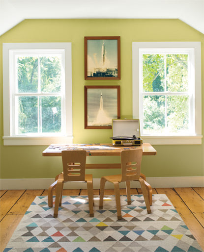 A kids' room with two windows features a portable turntable-topped desk set against a light green color wall.