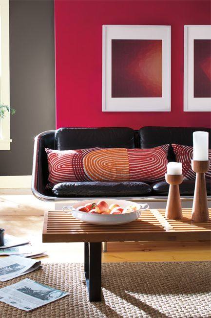 This casual living room includes a mod leather couch, slatted wooden coffee table, bold graphic framed prints and a bold, red-colored accent wall.