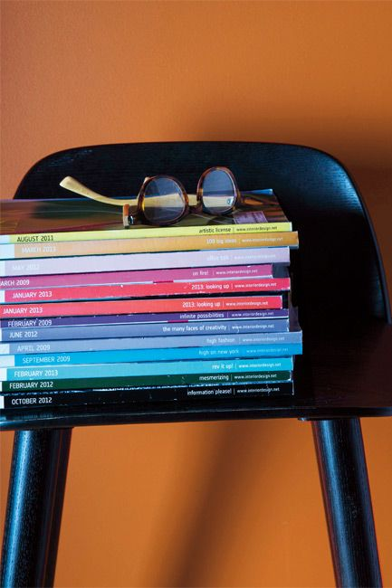 A black chair with a stack of multicolored magazines is set off by an orange wall.