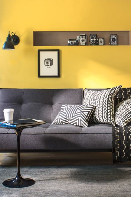 An armless gray couch and small, circular coffee table set against a yellow accent wall features black and white patterned pillows.