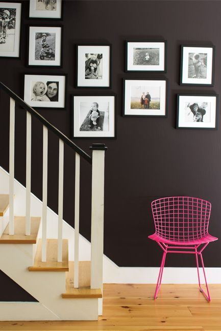 A staircase with banister is complemented by black and white family photos on the wall with a hot pink wire chair on the landing.