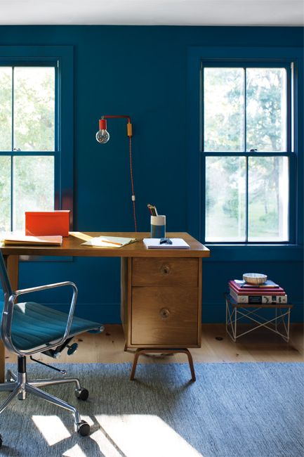 An office space features a mid-century modern wood desk complemented by varying shades of blue seen on walls, desk chair and rug.
