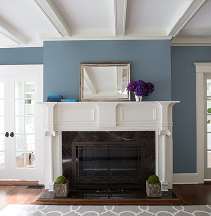 A white fireplace and mantel in a blue living room with windowed double doors.