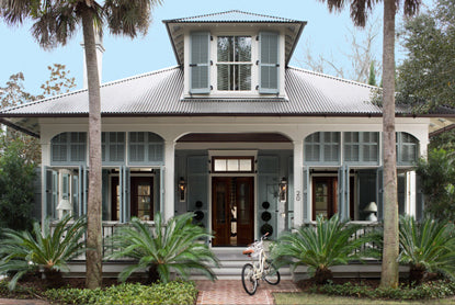 Light blue Key West-style home with front porch in tropical landscape.