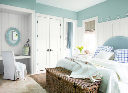 A light-blue painted bedroom with white trim and built-in vanity area.