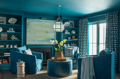 An all-blue painted living room with blue club chairs and built in shelving.