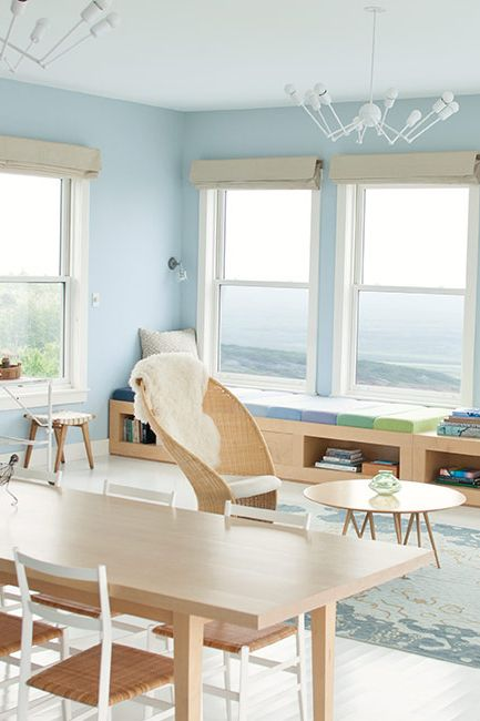 A light blue-painted room with sweeping views and a blonde wood dining table.