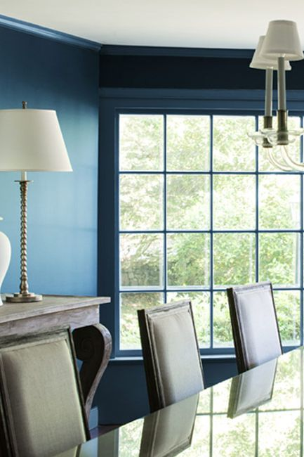 An all-blue painted dining room with chandelier.