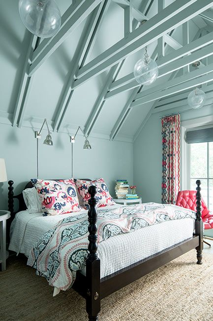 A blue-painted bedroom with four poster bed underneath vaulted ceilings.