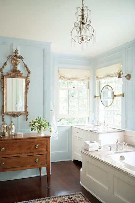 A light blue-painted bathroom with vintage mirror and sideboard.