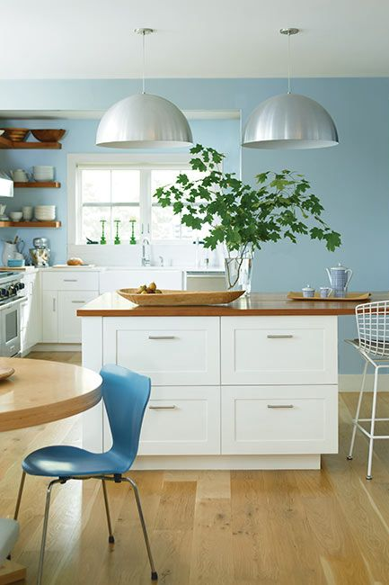 A contemporary kitchen with light blue-painted walls and white cabinets.