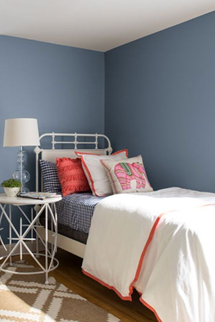 A bedroom with blue-painted walls and white trim with orange accents.