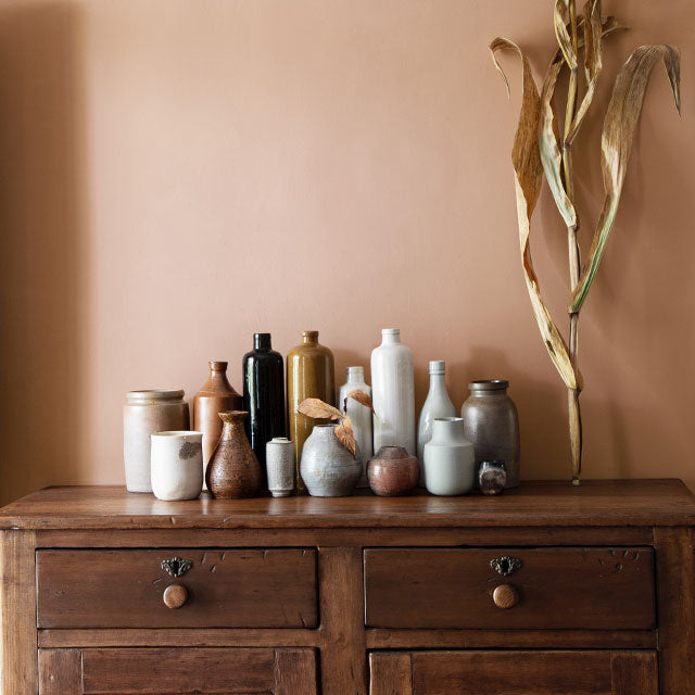 A collection of bottles on a wooden credenza in front of a gold-painted wall, with dried plant décor.