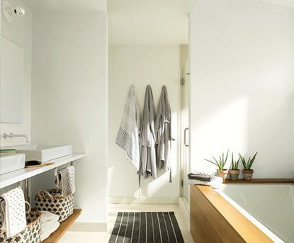 A white-painted bathroom with gray robes, wood-framed tub, boho baskets, and two sinks.