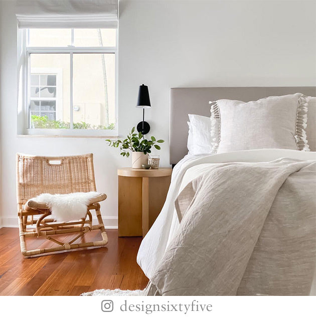 White-painted bedroom with gray bed linens, tasseled pillows, rattan chair with white fur throw, and wooden end table.