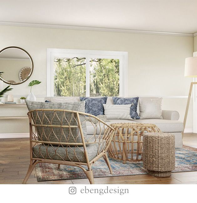 Boho living room with rattan chairs and coffee table, white sofa, lamp, stone fireplace, and round mirror.