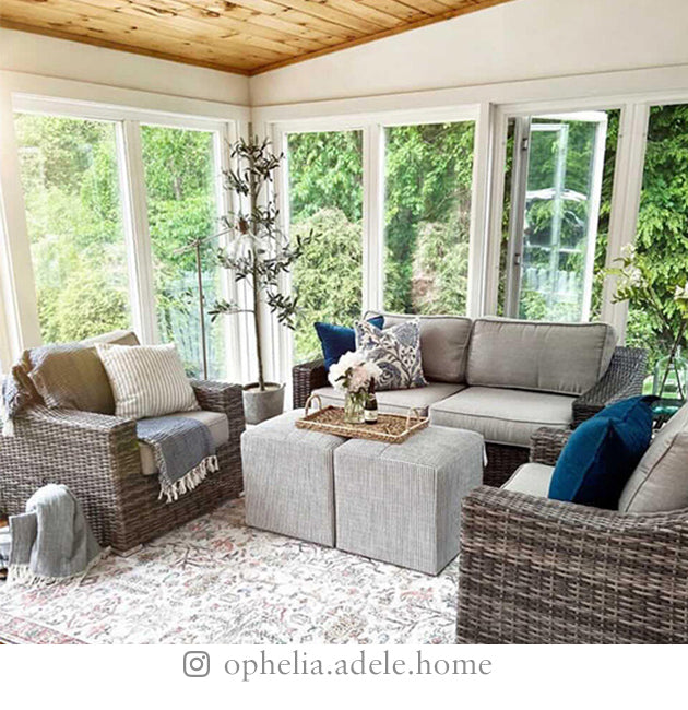 Sunroom with large windows, loveseat and two chairs, ottomans, rug, and various plants, surrounded by trees.
