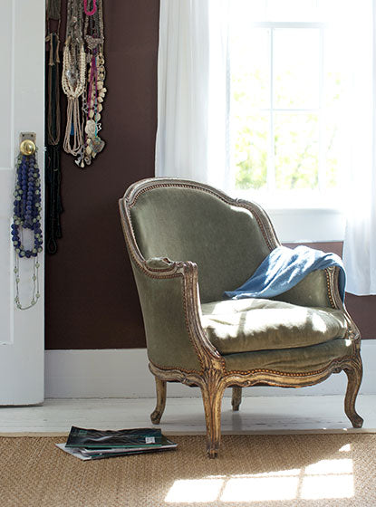 A gray vintage-style chair in a brown-painted room with various necklaces on the wall and hung on a doorknob on a white door.