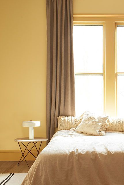 A gold-painted bedroom with a bed on a striped rug in front of a large window with beige curtains, featuring an end table and lamp.