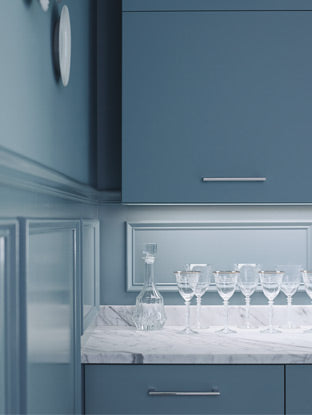 Monochromatic blue cabinets and blue walls are highlighted by a white marble countertop set with wine glasses.