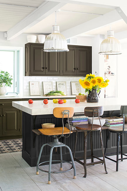 An airy industrial style kitchen taps into deep colors, from a black based kitchen island to deep green-brown cabinetry.