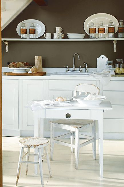 A cozy kitchenette is lovely in a deep neutral wall and white cabinetry.