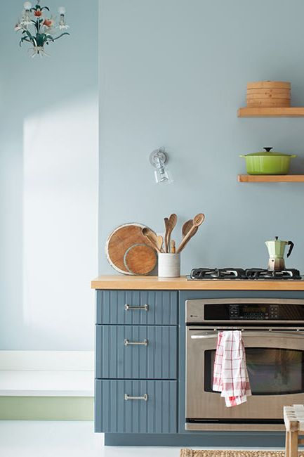 Cheery blue cabinets pair beautifully with blue walls in a minimalist kitchen.