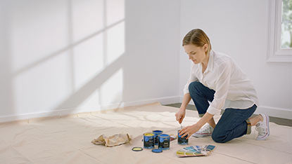 Woman opening paint cans