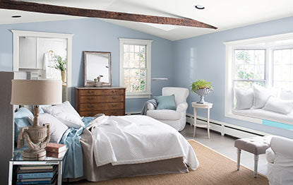 Bright bedroom with light blue walls and an exposed wood beam