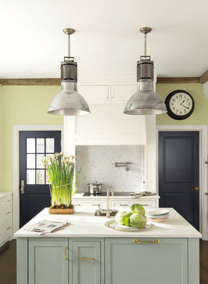 In this serene kitchen, a white, marble-topped island sits underneath two pendant lights in a kitchen painted in soft greens and off-whites.