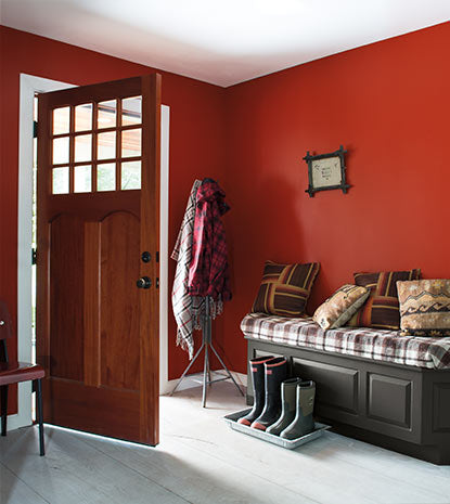 A deep red entryway does double duty as mud room with several pairs of boots lined up next to an upholstered bench.